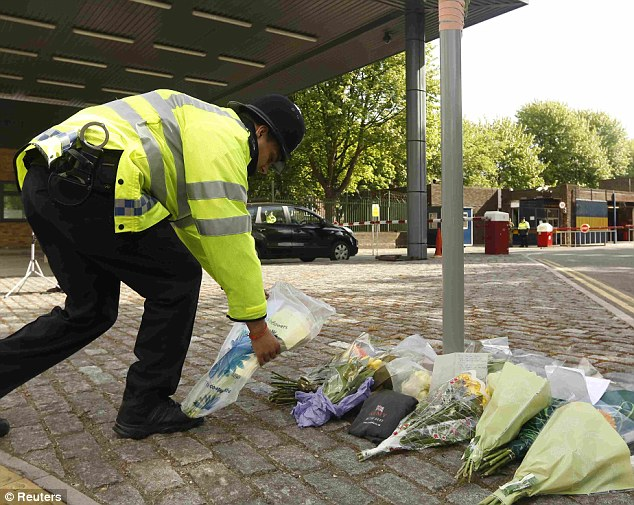 Grief: A police officer lays a bouquet of flowers outside the Royal Military Barracks today after the horrific killing yesterday