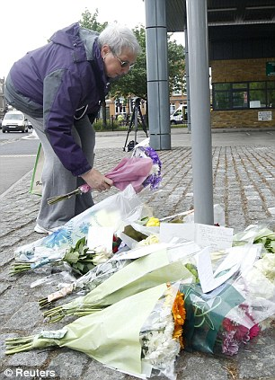 Tributes: A woman leaves flowers at the scene today following the killing which was condemned by the Muslim Council of Britain
