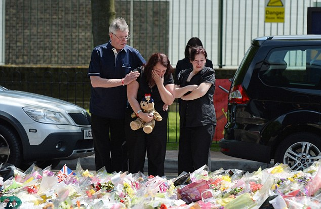 Heart-wrenching: Lyn Rigby, mother of Drummer Lee Rigby, and his stepfather Ian, view the flowers on display