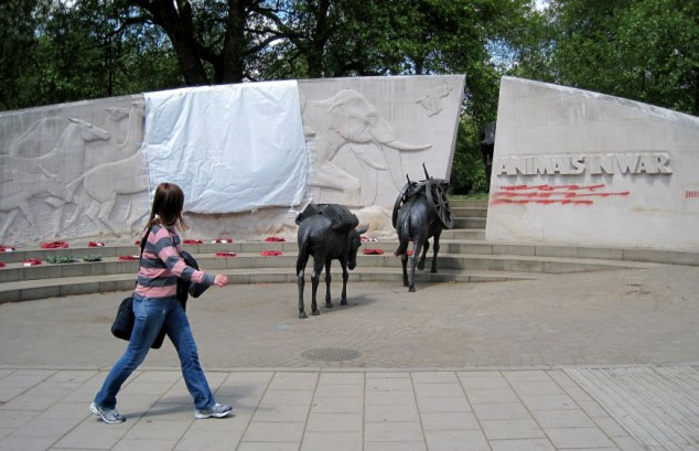 A tarpaulin covers part of the Animals in War Memorial on Park Lane, which police say they found at 5am