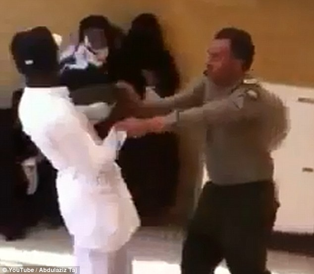 After hitting the man the immigration official pushes him backwards, as he attempts to clear the passport centre
