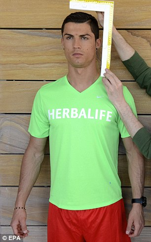 Big head? The Real Madrid player earlier covered up his buff body under a green T-shirt as the measurements got underway