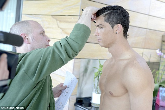 And pose: Cristiano happily stripped to show off his naked torso as they readied his upcoming wax work