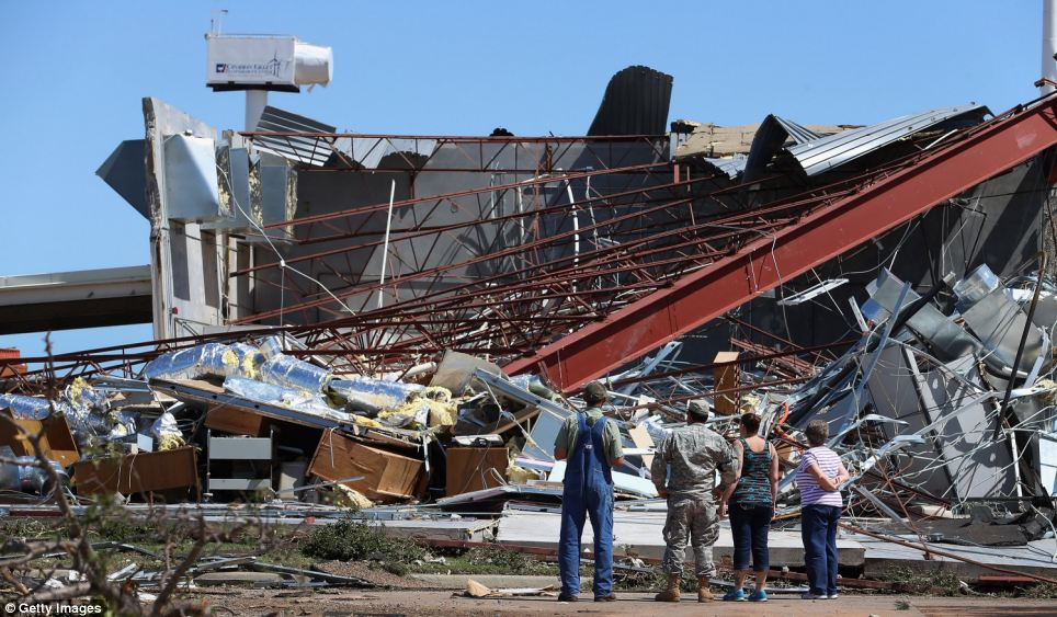 People survey the damage at the Canadian Valley Technology Center's El Reno Campus after it was hit by a powerful tornado on Friday
