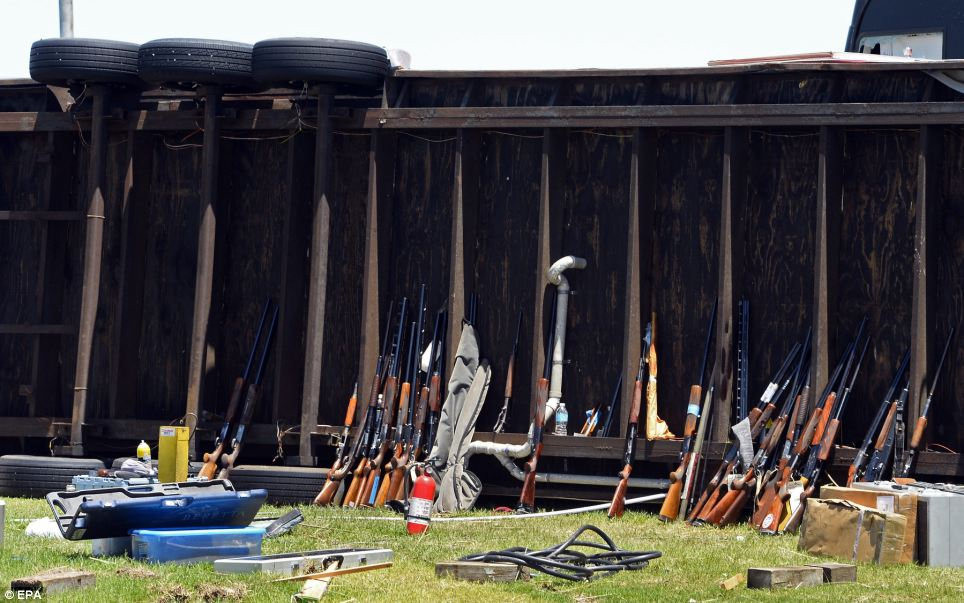 Shotguns recovered from a field lay against a overturned trailor at a state shooting tournament that was destroyed in El Reno