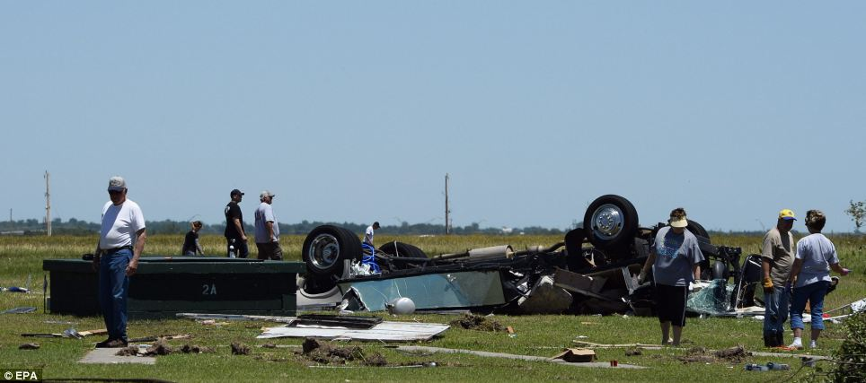People search a field for guns near a destroyed RV at a state shooting tournament that was destroyed in El Reno