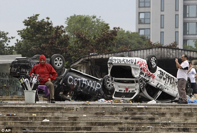 Wreckage: A street vendor sells umbrellas in front of destroyed police cars in Taskim square in Istanbul