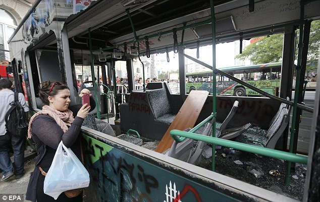Ruin: A woman takes pictures of a public bus which has been left a wreckage after violent protests in Turkey