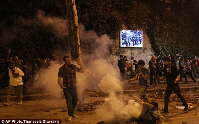Riot: A protester falls down as he tries to throw back at police a tear gas canister