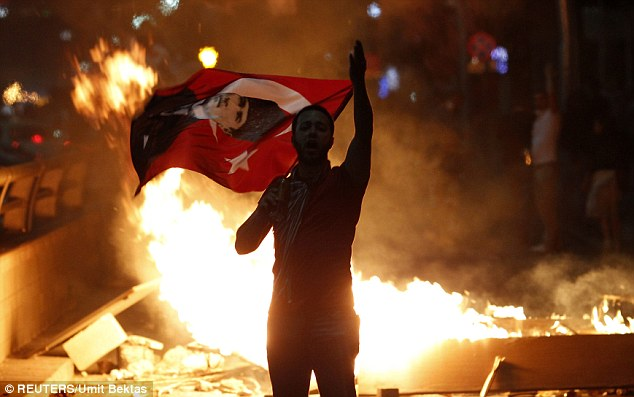 Blaze: An anti-government protester holds Turkey's national flag with a portrait of Mustafa Kemal Ataturk on it