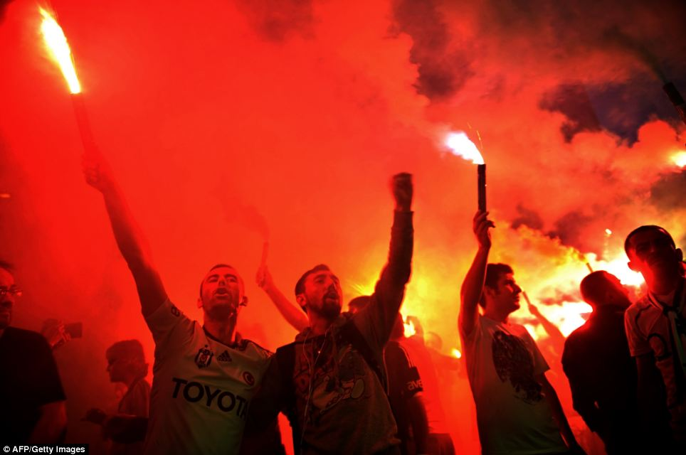 Carnival atmosphere: The glow of red flares illuminates the scene as protesters stand outside in Istanbul tonight. The brutal response of police has raised concerns from the U.S., the EU and human rights groups