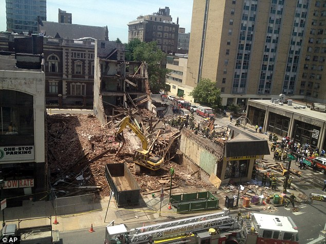 Collapse: Emergency personnel respond to a building collapse in downtown Philadelphia, where the city fire commissioner says 13 people were pulled from the rubble and one person is still trapped