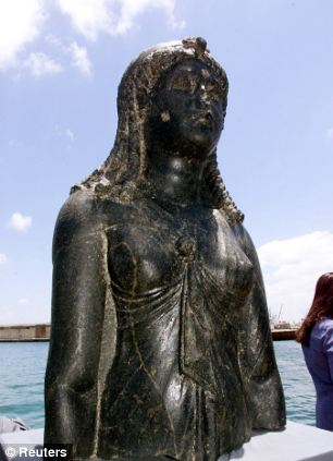 The statue of the Goddess Isis sits on display on a barge in an Alexandrian naval base