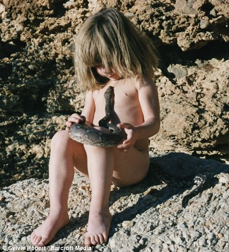 No fear: The young child cradles a rock python snake