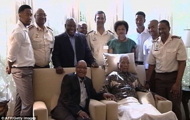 Ailing: President Jacob Zuma places a hand on Mr Mandela's, whose head was supported by a pillow and knees covered by a blanket following his release from hospital in April