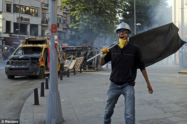 A protester shouts as Turkish riot police fired water cannon and tear gas during heated clashes in Istanbul today