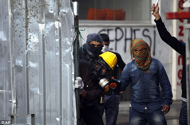 Protesters check for riot police from behind a barricade during violent clashes in Istanbul this morning