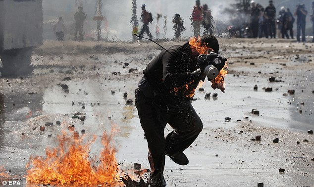 A protester is on fire after a Molotov cocktail goes off during a clash with riot police in Istnabul this morning