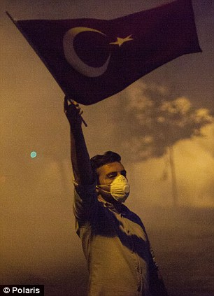 Defiant: A youth waves a flag during clashes with police after the operation at Gezi Park