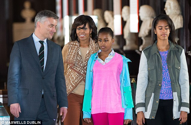 Happy holidays! Sasha and Malia Obama look a little bored as they are shown the historic books at Trinity College by Dr Patrick Prendergast
