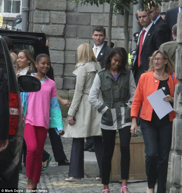 Under watchful eyes: The Obama girls are followed by their heavy security details as they visit Trinity College in Dublin today