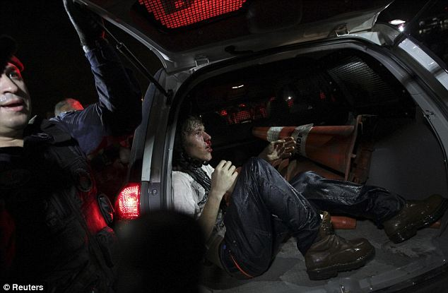 Pain: An injured demonstrator sits in a police van after he was arrested during a protest in Brasilia