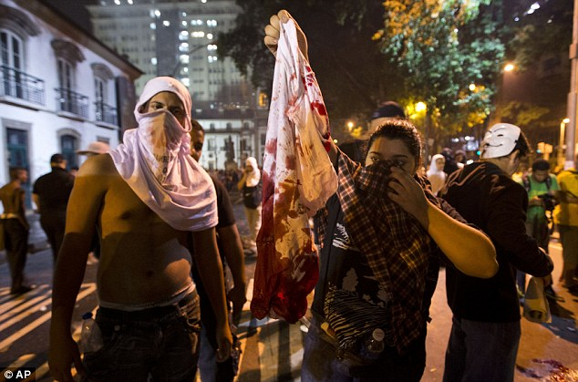 Hurt: Protesters hold the blood-stained T-shirt of a protester who was shot in the shoulder during a demonstration in Rio de Janeiro