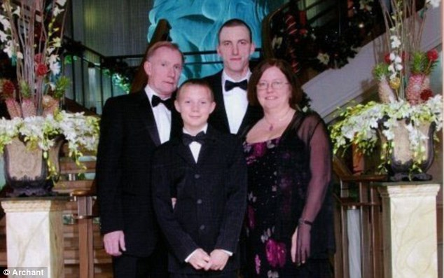 Happier times: Michael, at the back, pictured with his mother, Linda, stepfather Andy and his younger brother