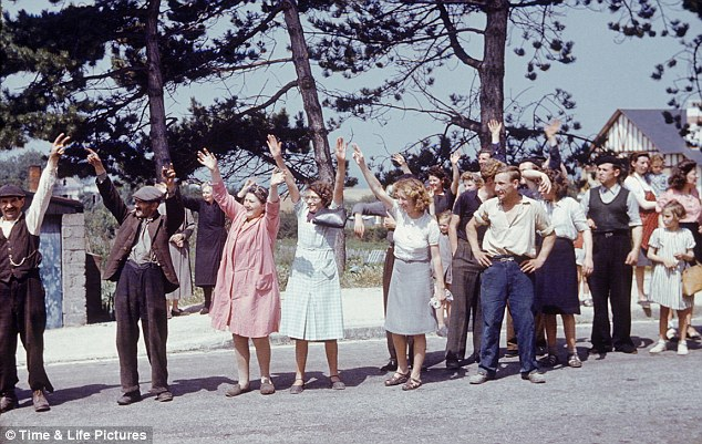 In the wake of World War II's D-Day invasion, French townspeople wave at arriving Allied forces, Normandy, France, 1944