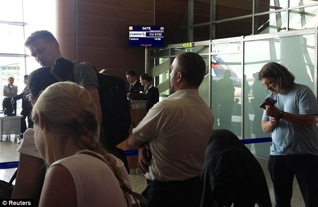 Where is he? Passengers queue on Monday to board a plane to Cuba at a terminal of Moscow's Sheremetyevo airport. But Edward Snowden was nowhere to be seen despite being booked on the flight