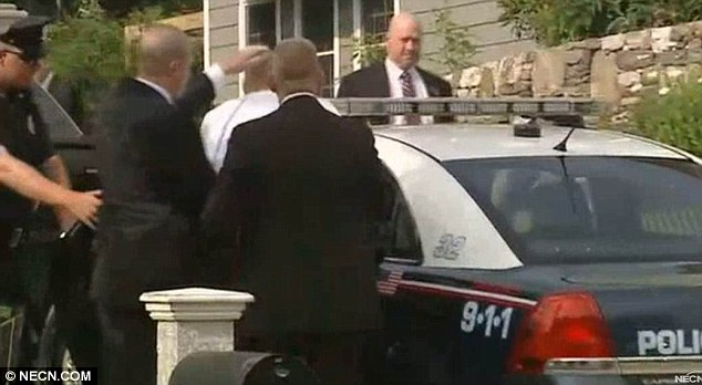 Trouble: Police push Hernandez's head into the squad car as news emerged that the Patriots had released him