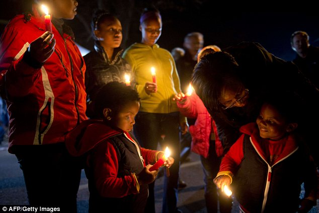 Touching: Children light candles as they take part in a candlelit vigil for Mr Mandela