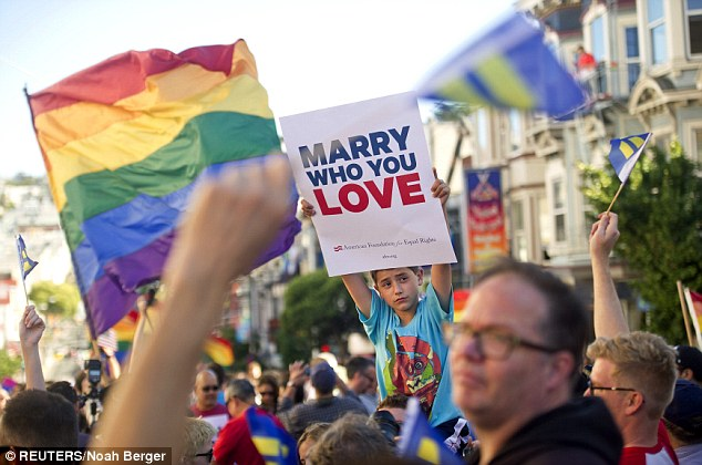 Enzo Catalano, 9, holds up a sign amongst thousands of revelers at Castro St. in San Francisco, California after the United States Supreme Court delivered the ruling