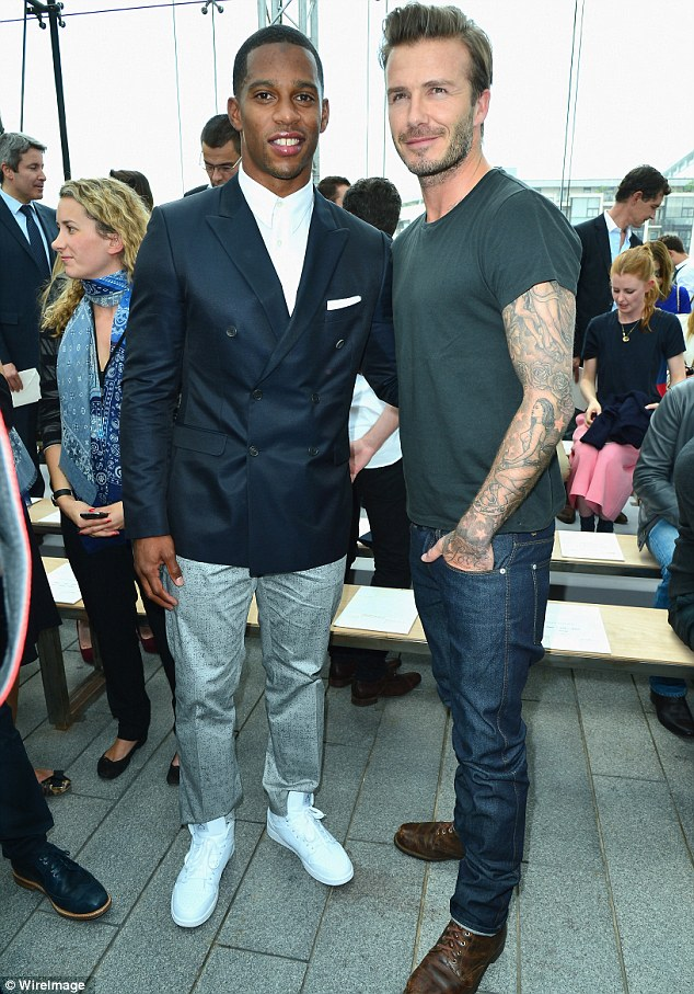 Sporting pals: Becks posed up with Victor Cruz ahead of the show starting during fashion week