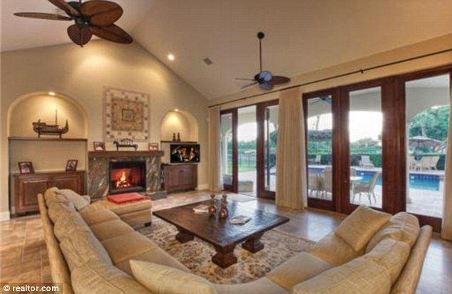 Cosy: The living room has a fireplace and French doors opening on to the patio and pool