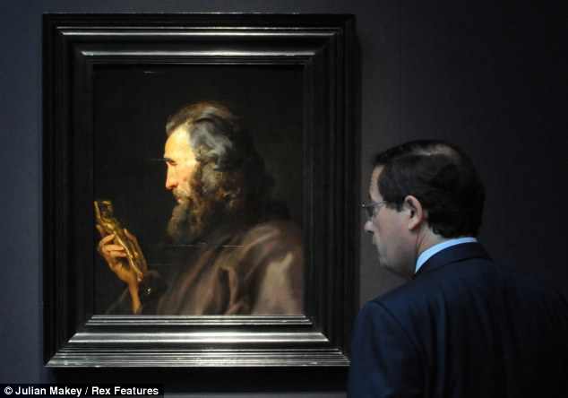Art of all ages: A man admires 'Head of a Bearded Man Holding A Bronze Figure', a painting by Sir Peter Paul Rubens, ahead of the auction at Christie's