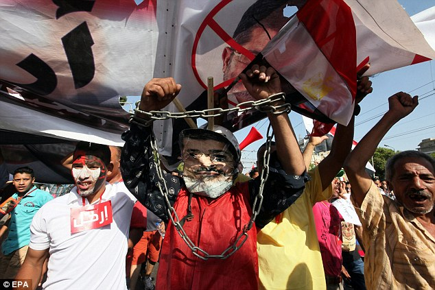 Egyptians opposing President Morsi wave their national flag while one of them wears chains and a face mask