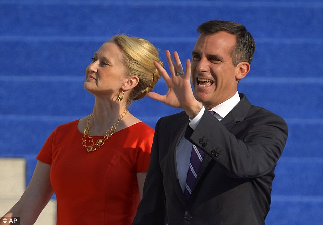 Waving to the crowd: Garcetti, right, waves as his wife Amy Wakeland looks on as they are introduced before he is sworn in as mayor