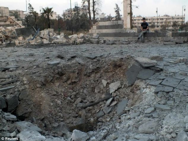 Crater: A man sits next to the damaged area outside Khalid bin al Walid Mosque in Homs