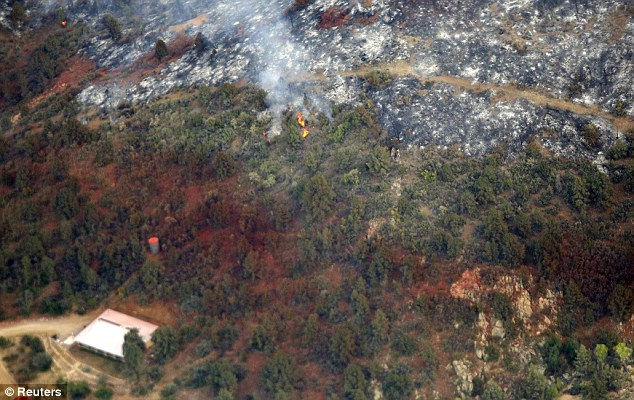 Smoke: Smoke was still seen and flames still burned on Monday after the devastating wild fires