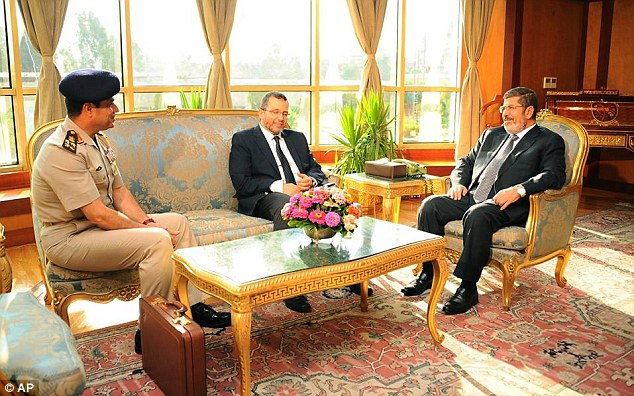 Not backing down: President Mohammed Morsi, shown right in this picture released yesterday, meets with Prime Minister Hesham Kandil, center, and Egyptian Minister of Defense, Lt Gen Abdel-Fattah el-Sissi, left, in Cairo