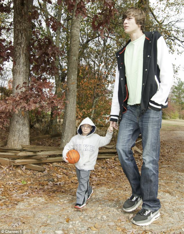 Nick's younger brother Travis (pictured) towers above him at 6 ft 5 inches tal