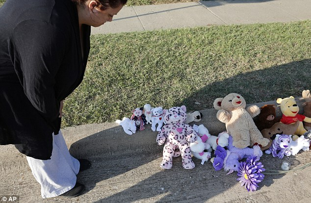 Coping: Neighbors quickly set up a makeshift memorial on the curb for the little girl. It was torched along with the family's car Friday