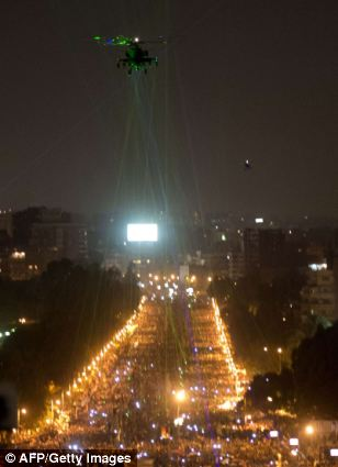 Troubling: Images have emerged of protesters apparently trying to bring down a military helicopter with laser pointers during protests in Cairo as trouble in Egypt escalated overnight