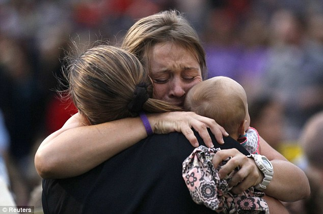 Hugs: A woman holding a baby hugs another person seated in the section reserved for immediate family of the 19 firefighters killed in a nearby wildfire in Prescott