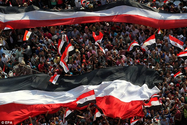 Egyptian protesters hold giant national flag as they demonstrate against the President Mohamed Morsi, in Tahrir Square, Cairo