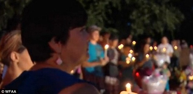 Mourning: About 100 people turned out for a candle-light vigil to mourn the little girl ground brutally murdered