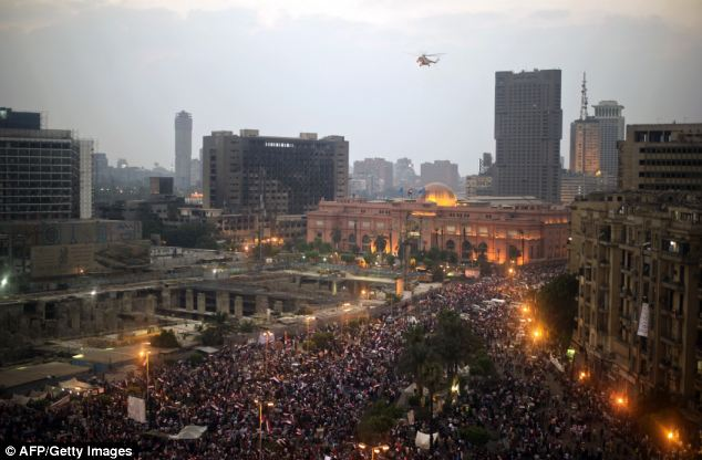 An Egyptian army helicopter flies over protestors in Cairo's landmark Tahrir Square