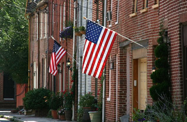 Patriotic: Residents in Baltimore, Maryland, hang flags above their doors for July 4th in the Fells Point neighbourhood