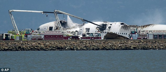 Blaze: Fire trucks spray water on the plane which crash landed and caught fire as it arrived in San Francisco